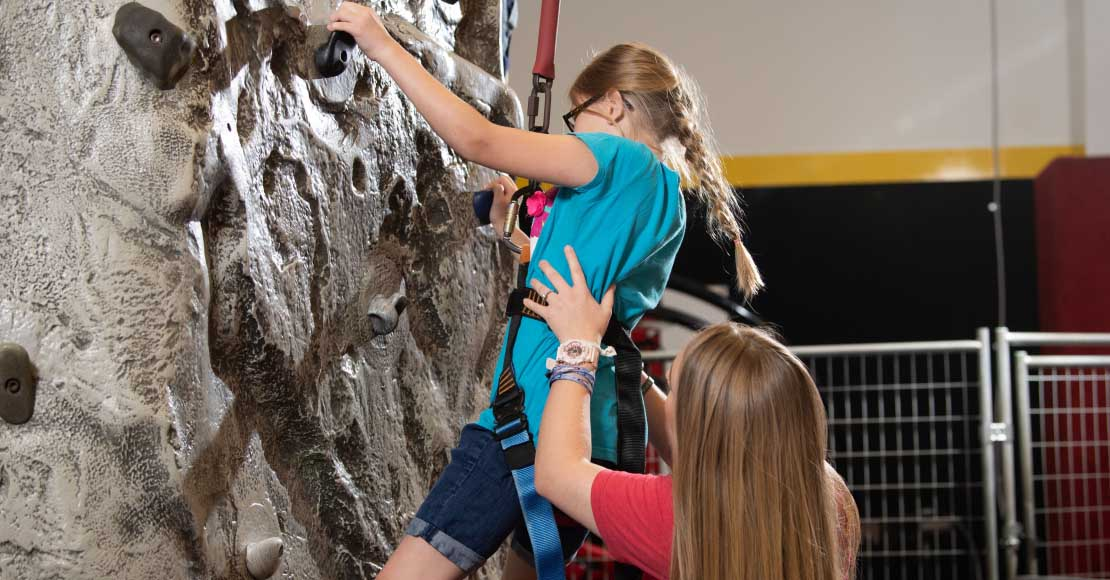 kid being assisted at the rock wall